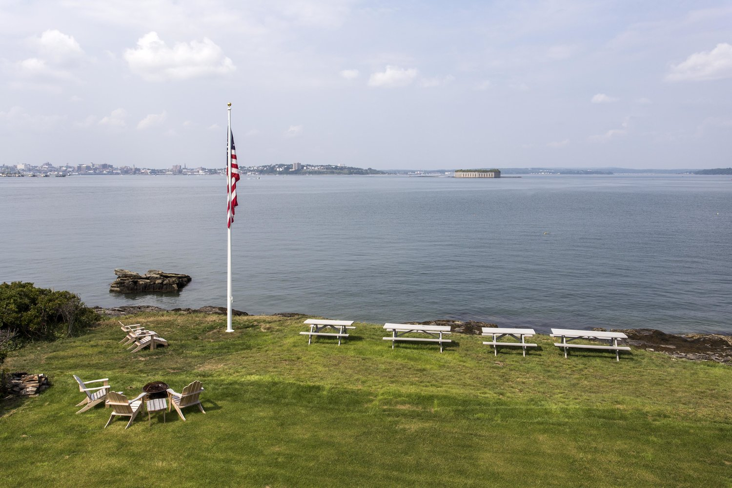 Green grass lawn with American flag at Cappy's Lodge overlooking Casco Bay.