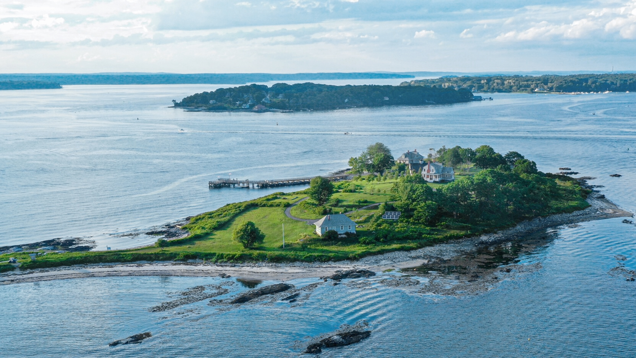 House Island aerial view with Sunshine Cottage and Sea Glass Beach in the foreground and the island's splendid greenery and tress surrounded by Casco Bay